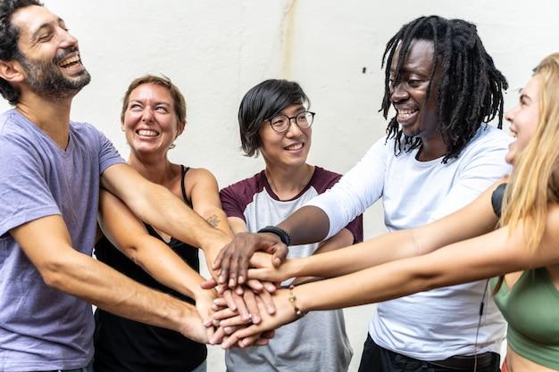 Groupe de jeunes de différentes ethnies souriant et mettant la main ensemble
