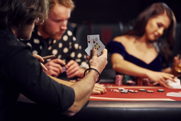 Groupe de jeunes élégants qui jouent au poker au casino ensemble
