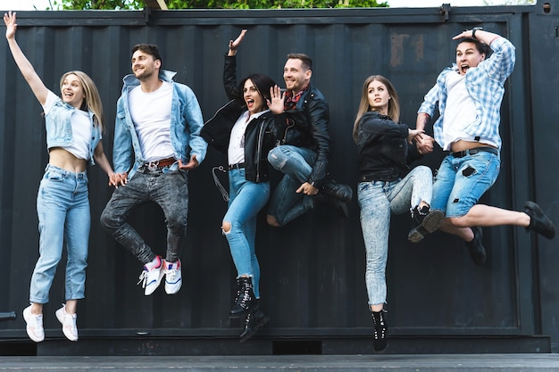 Groupe de jeunes et élégants sautant en l'air dans une rue de la ville