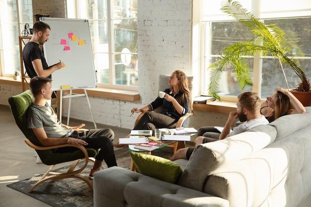 Groupe de jeunes employés de bureau caucasiens se réunissant pour discuter de nouvelles idées. rencontre créative. travail d'équipe et brainstorming. les hommes et les femmes se réunissent au bureau pour planifier leur futur travail. concept d'entreprise.