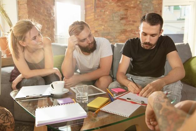 Groupe de jeunes employés de bureau caucasiens se réunissant pour discuter de nouvelles idées réunion créative