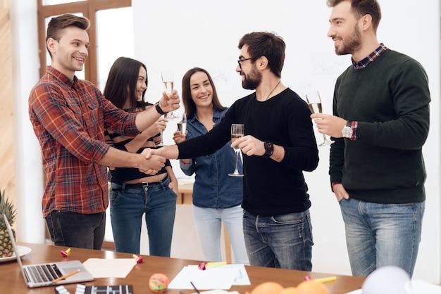 Un groupe de jeunes employés de bureau en fête.