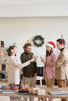 Groupe de jeunes employés de bureau joyeux dans des vêtements décontractés intelligents et des bandeaux de noël grillant avec du champagne sur une table avec des collations et des cadeaux