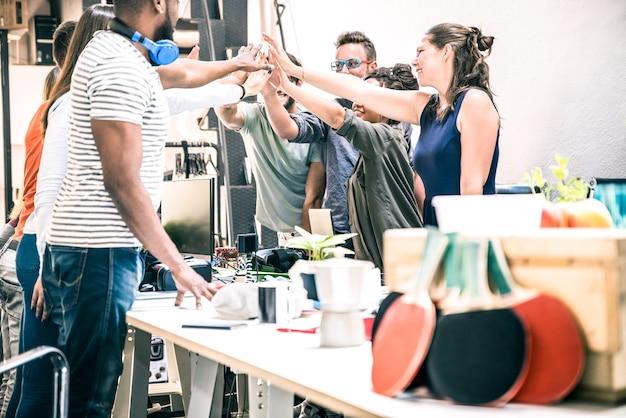 Groupe de jeunes employés en démarrage empilant les mains dans un studio urbain