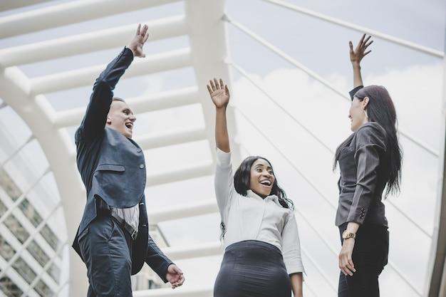 Groupe de jeunes entrepreneurs heureux avec les mains dans les airs succès sur leurs plans.