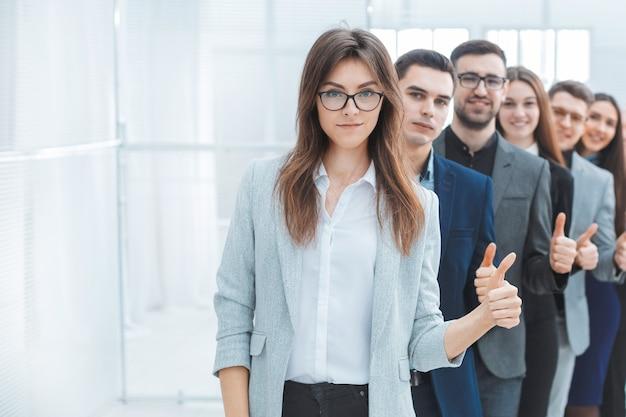 Groupe de jeunes entreprises montrant les pouces vers le haut. le concept de travail d'équipe