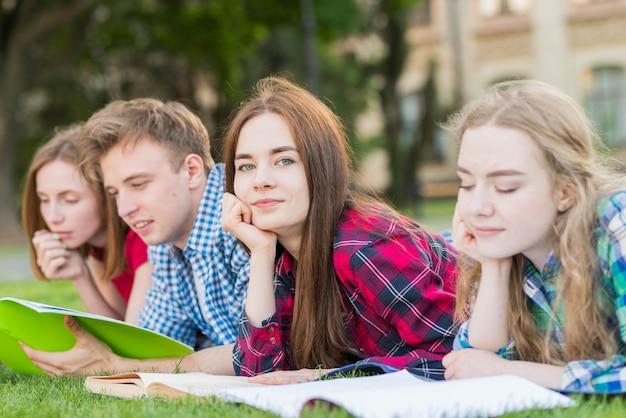 Groupe de jeunes étudiants apprenant dans un parc