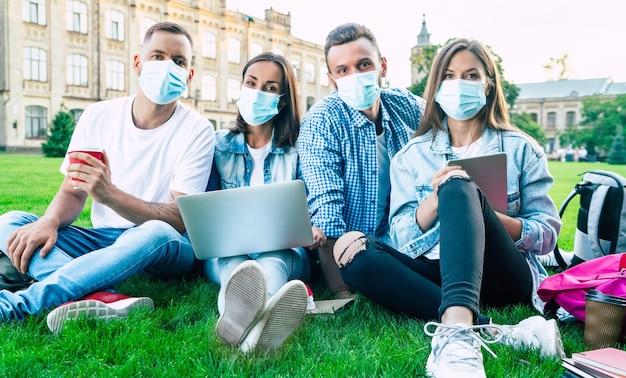 Groupe de jeunes étudiants portant des masques médicaux avec ordinateur portable et livres étudient ensemble à l'université. amis à l'extérieur assis sur l'herbe.