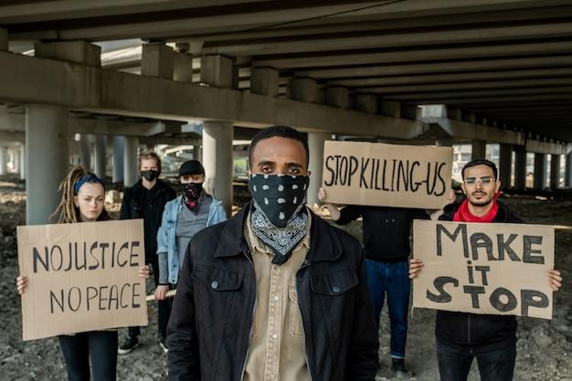 Groupe de jeunes extrémistes multiethniques en tête d'homme noir avec bandana sur le visage debout avec des bannières sous le pont