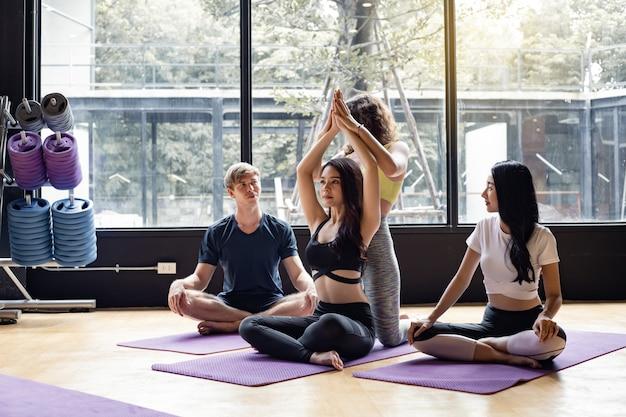 Groupe de jeunes faisant du yoga sur un tapis de yoga avec un entraîneur enseignant progressivement.