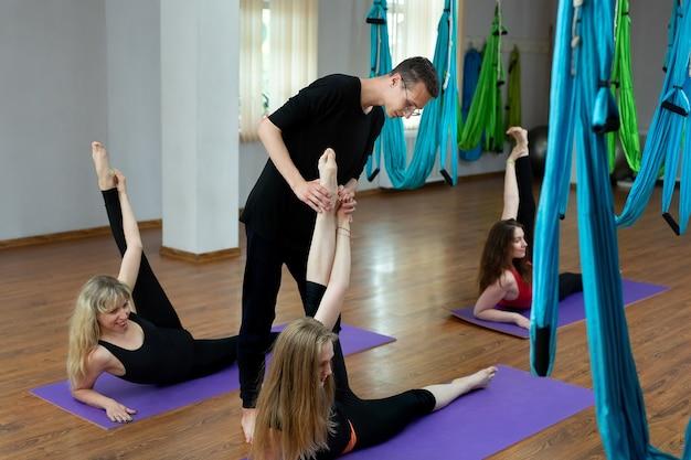 Un groupe de jeunes fait du yoga dans la salle de gym sur des nattes, des étirements et des exercices de relaxation. forme et bien-être.