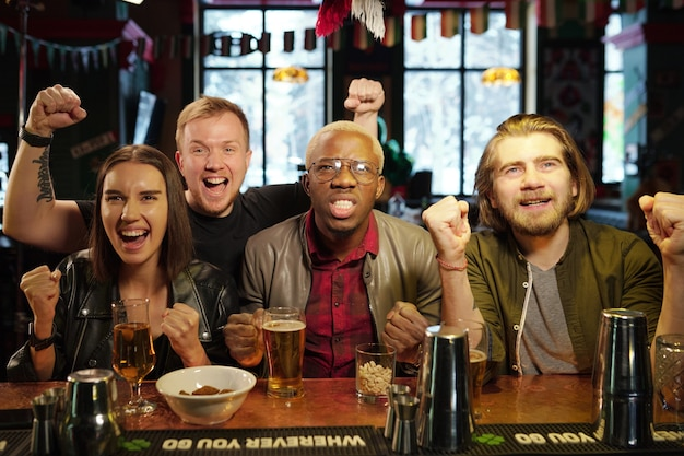 Groupe de jeunes fans de football extatiques interculturels en tenue décontractée debout près du comptoir du bar avec boissons et collations pendant la diffusion de football au pub