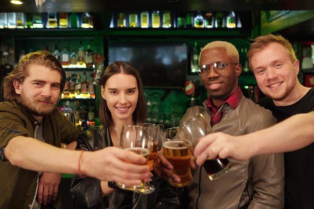 Groupe de jeunes fans de football heureux trinquant avec des verres de bière devant la caméra tout en célébrant la victoire de leur équipe de football préférée