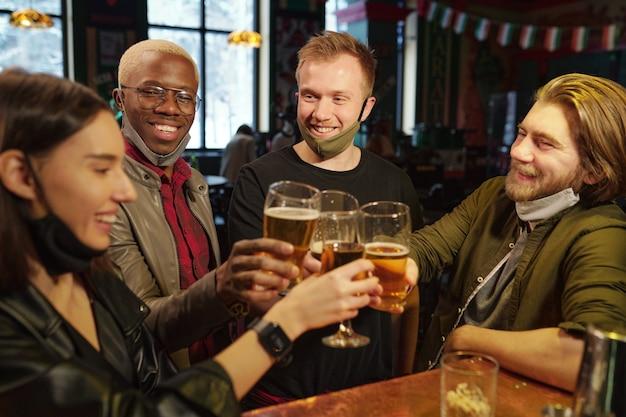 Groupe de jeunes fans de football interculturel trinquant avec des verres de bière au comptoir du bar tout en célébrant la victoire de leur équipe de football préférée