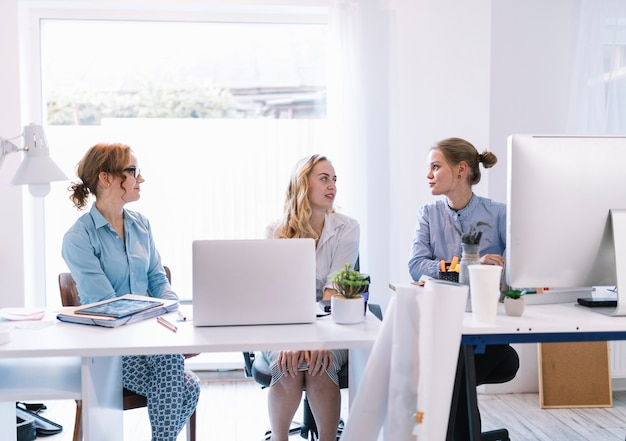 Groupe de jeunes femmes d'affaires assis dans un bureau moderne se parlant