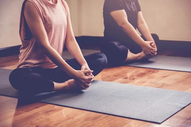 Groupe de jeunes femmes asiatiques en bonne santé pratiquant leçon de yoga avec instructeur en home studio