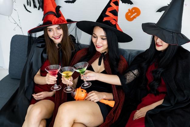Groupe de jeunes femmes asiatiques en costume de sorcière célébrant la fête dans la salle pour le thème halloween à la maison. gang teen thai avec fête d'halloween avec le sourire. concept de fête halloween à la maison.