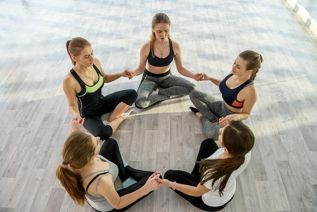 Groupe de jeunes femmes assises sur le sol en cours de yoga