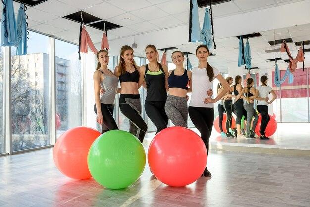 Groupe de jeunes femmes dans une salle de sport avec des ballons de fitness