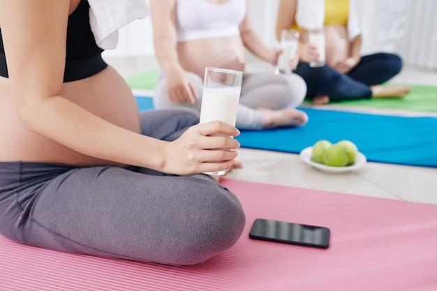 Groupe de jeunes femmes enceintes assises sur des tapis de yoga dans un club de santé, buvant du yaourt, mangeant des fruits et discutant de la grossesse