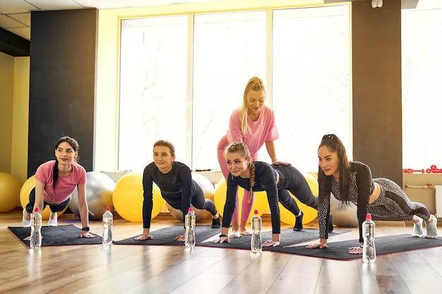 Groupe de jeunes femmes faisant planche ensemble dans une salle de sport
