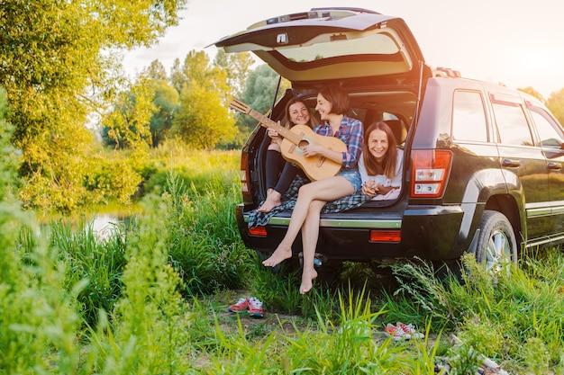 Un groupe de jeunes femmes gaies voyage dans la nature en voiture
