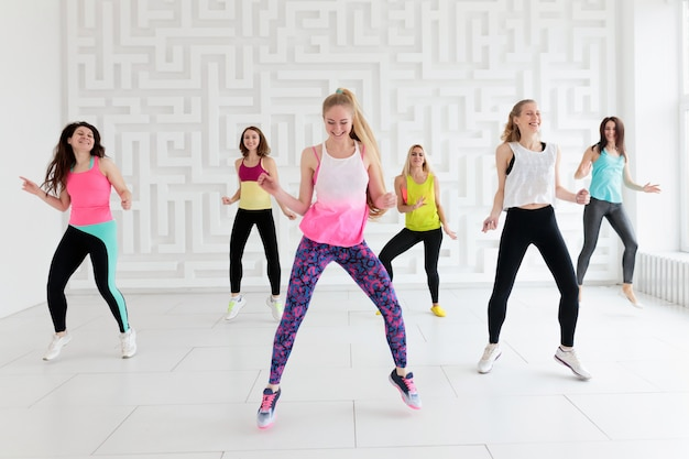 Groupe de jeunes femmes heureux en vêtements de sport au cours de danse de fitness en studio de fitness blanc