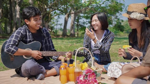 Groupe de jeunes femmes et hommes assis, mangeant et jouant de la guitare dans le parc au printemps été