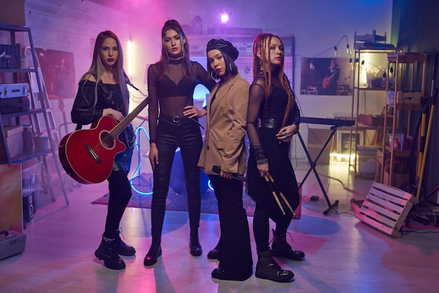 Groupe de jeunes femmes avec des instruments de musique debout en studio