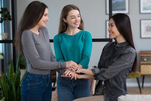 Groupe de jeunes femmes positives, main dans la main