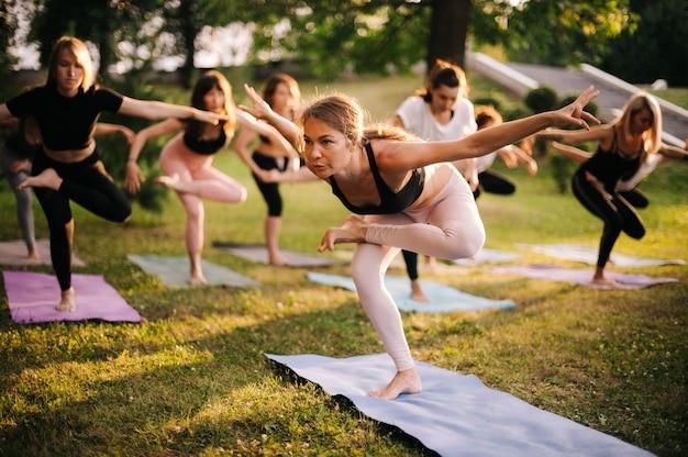 Un groupe de jeunes femmes en vêtements de sport se tient dans l'une des positions de yoga sur une jambe le matin dans le parc au lever du soleil. groupe de personnes méditant. les rayons du soleil brillent à huis clos
