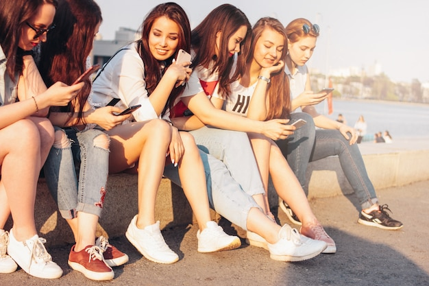 Groupe de jeunes filles heureuse, vrais amis, étudiants, utilisation, mobile, à, rue ville