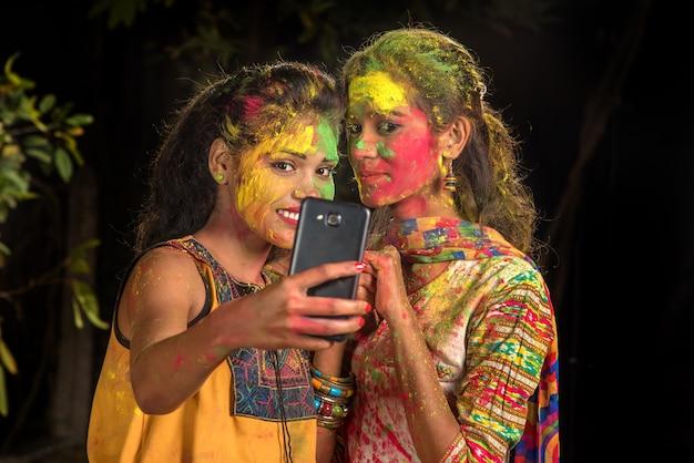 Groupe de jeunes filles heureuses s'amusant et prenant selfie à l'aide de smartphone sur le festival holi. concept de festival et de technologie