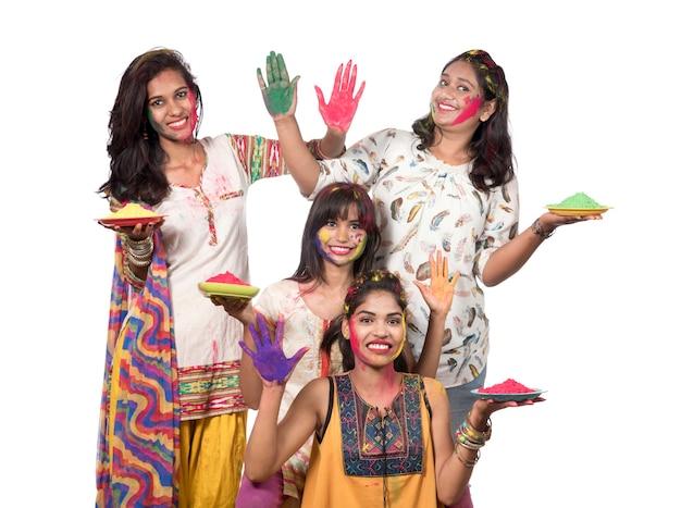 Groupe de jeunes filles heureux s'amusant avec de la poudre colorée au festival de couleurs holi