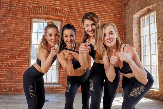 Groupe de jeunes filles sportives se reposant après une séance d'entraînement dans un studio loft spacieux. amitié féminine dans la salle de gym, détente après la remise en forme, à l'intérieur, effet d'éblouissement du soleil.