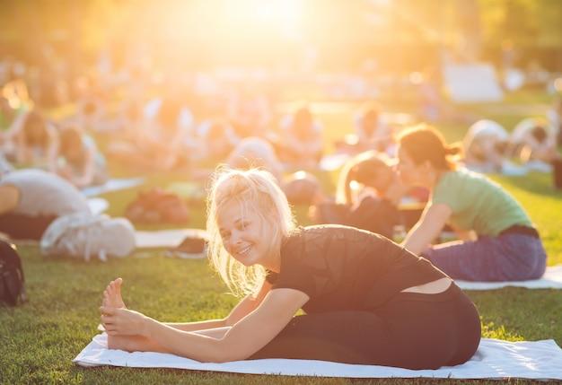 Un groupe de jeunes font du yoga dans le parc au coucher du soleil.