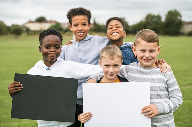 Groupe de jeunes garçons montrant des papiers vierges