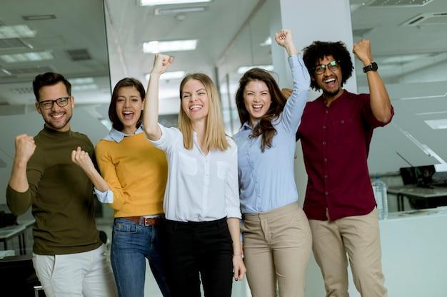 Groupe de jeunes gens d'affaires excités avec les mains debout dans le bureau
