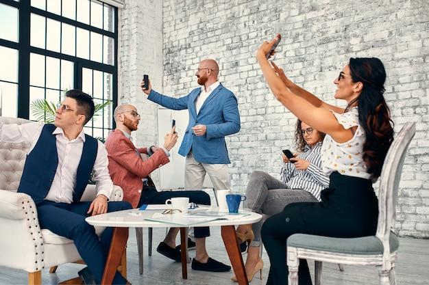 Groupe de jeunes gens d'affaires multiethniques faisant selfie avec téléphone après leur travail sur un nouveau projet.