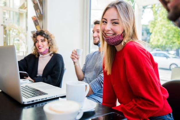 Groupe de jeunes gens d'affaires portant un masque facial réunis pour discuter d'une idée créative