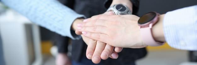 Groupe de jeunes gens d'affaires se pliant les mains ensemble agrandi.