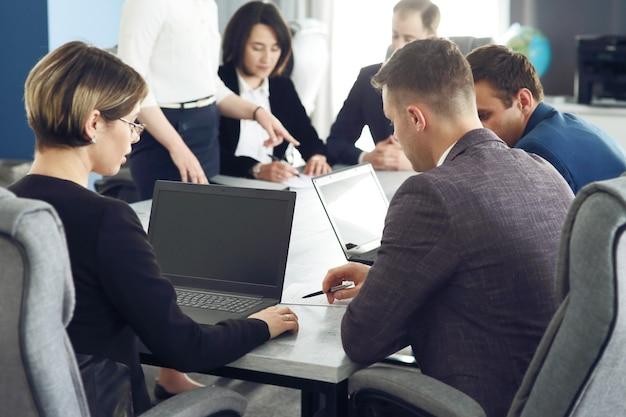 Groupe de jeunes gens d'affaires se réunissant au bureau s'amusant ensemble à discuter d'une idée
