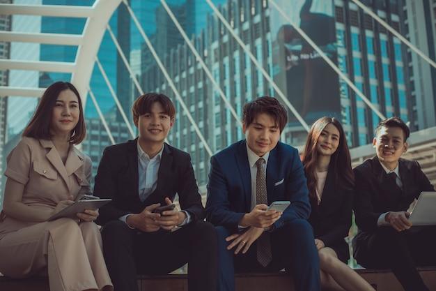 Groupe de jeunes gens d'affaires souriant et regardant la caméra