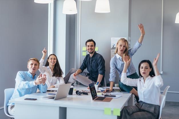 Groupe de jeunes gens d'affaires à une table agitant leurs mains joyeusement en regardant la caméra