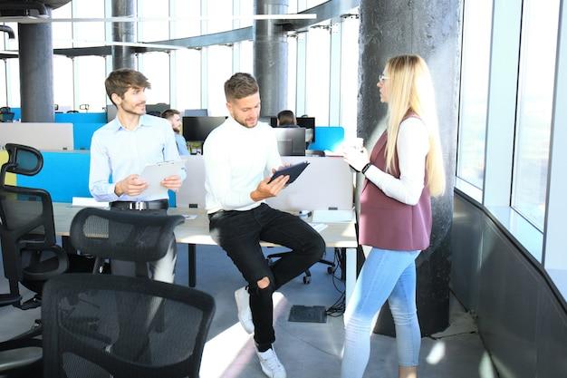 Groupe de jeunes gens d'affaires travaillant et communiquant ensemble dans un bureau créatif.
