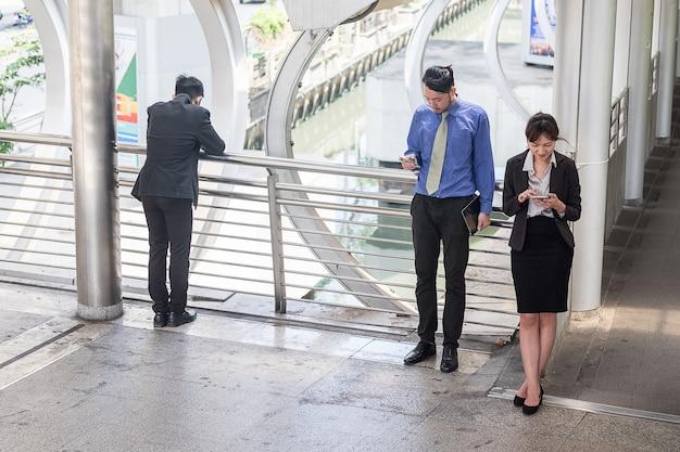 Groupe de jeunes gens d'affaires utilisent leur téléphone