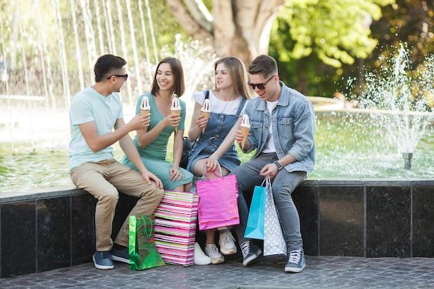 Groupe de jeunes gens attrayants, faire du shopping. amis à l'extérieur tenant un sacs à provisions et souriant. amis joyeux ensemble.