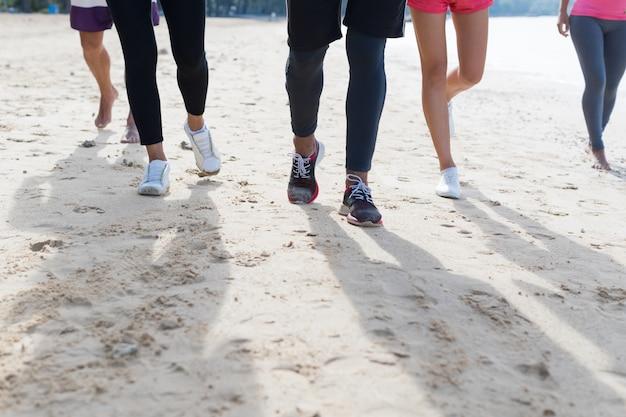 Groupe de jeunes gens courir sur la plage pieds sport gros plan jogging travailler entraînement en équipe