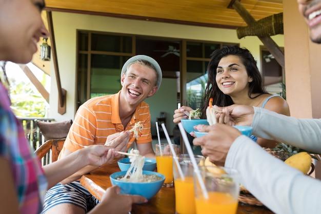 Groupe de jeunes gens discutant en mangeant des nouilles soupe traditionnelle asiatique
