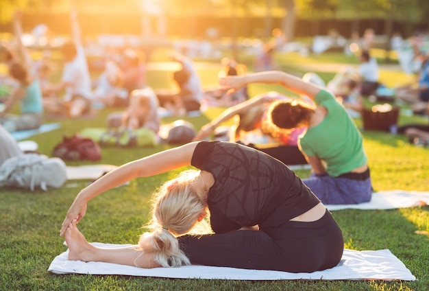 Un groupe de jeunes gens font du yoga dans le parc au coucher du soleil.